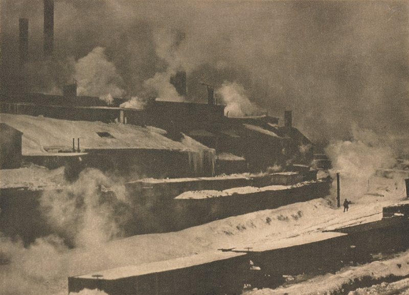 factory in winter, with a train in the foreground and a lone figure walking in the lower right