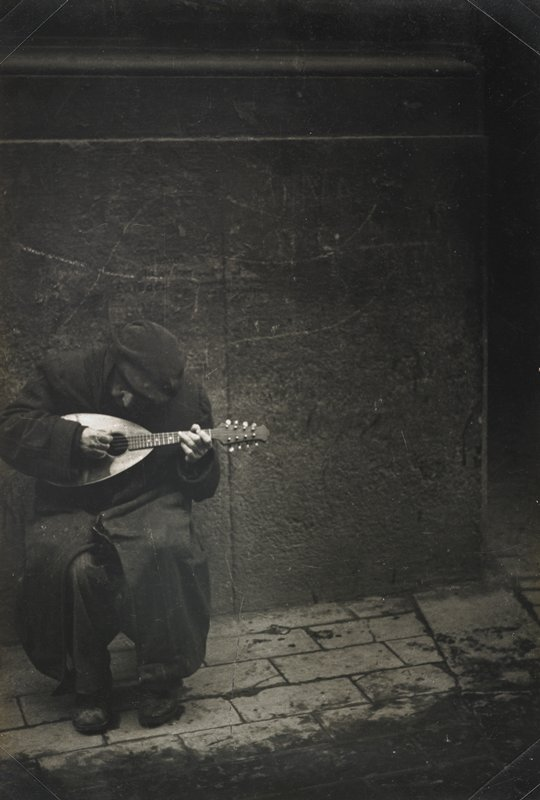 dark image of a man at left, seated and hunched over, wearing dark coat and hat, playing the mandolin; scratched wall; stone pavers; mounted on masonite