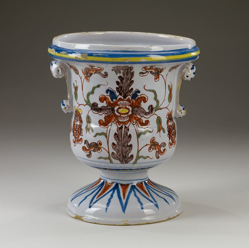 vase with wide domed foot; urn-shaped body flaring outward to spool mouth; pair of decorative scroll handles; decorated in purple, rust, green, blue and yellow on white; floral designs on body; repeating triangles and wavy lines on foot