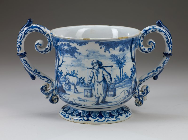 large footed cup with two handles; landscape with man carrying buckets on a yolk; woman behind milking cow; rocks with flowers and flying bird above at R on opposite side; foliate design on handles and around base