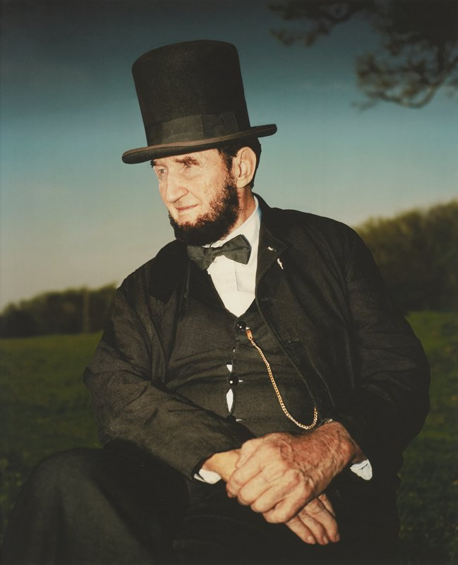 portrait of blue-eyed, bearded man dressed as President Lincoln; man seated looking to PR with clasped hands resting in lap on PL thigh; gold watch chain attached to vest; wheat tassel inserted though hole in PL lapel; blurry line of trees and blue sky in distance; blurry tree branch in URC; framed behind glass in black wood frame; one of a set of 18 photographs to be displayed together