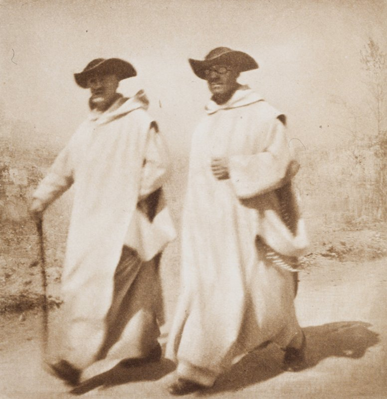 two priests walking on dirt road; both wear white robes and black hats; one wears glasses, the other walks with cane