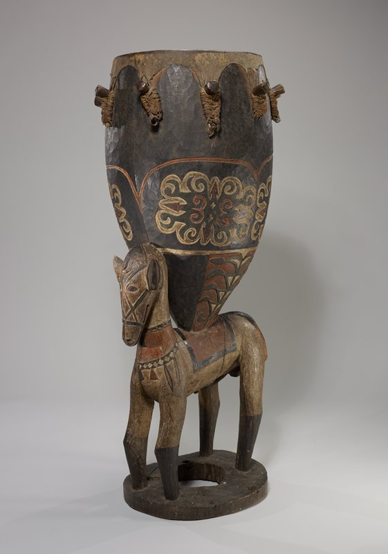 horse on doughnut-shaped base supporting bullet-shaped drum on its back; horse has carved details of bridle, saddle, and neck ornament; drum has organic curvilinear decorations; heightened in red, white and green pigments; large pegs hold drum head onto drum body; each portion of drum head below pegs are wrapped in plant fibers