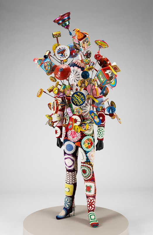 a: wire framework in organic shape with printed tin, plastic and wooden toys and noisemakers attached--Jack-in-the-boxes, various shapes of noisemakers, drums, clickers, tops and tambourines; b: suit installed over black plastic mannequin; colorful sweater fragments pieced together to create a bodysuit with head and face covering; bodysuit covered overall with crocheted doilies and hot pads, embroidered felt fragments and pieced stitched pieces; pink and white doily over face area