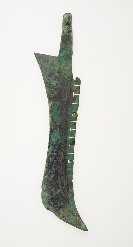 A flange with alternating straight and T-shaped scores of the type commonly found on early ritual vessels decorates the upper idge of this weapon. Along the blade proper, just below the flange, is a band of head-turning dragons with bottle horns on a ground of squared spirals. This decor is in low relief. Patina green.