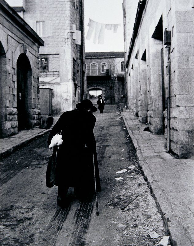 man dressed in long black coat and black hat seen from behind, walking with a cane through a narrow street carrying a chicken under his proper left arm