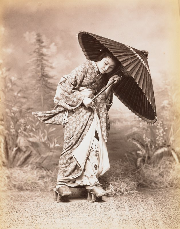 "young woman dressed in patterned kimono, holding a parasol and wearing shoes similar to ""geta"" sandals but with an enclosed toe"