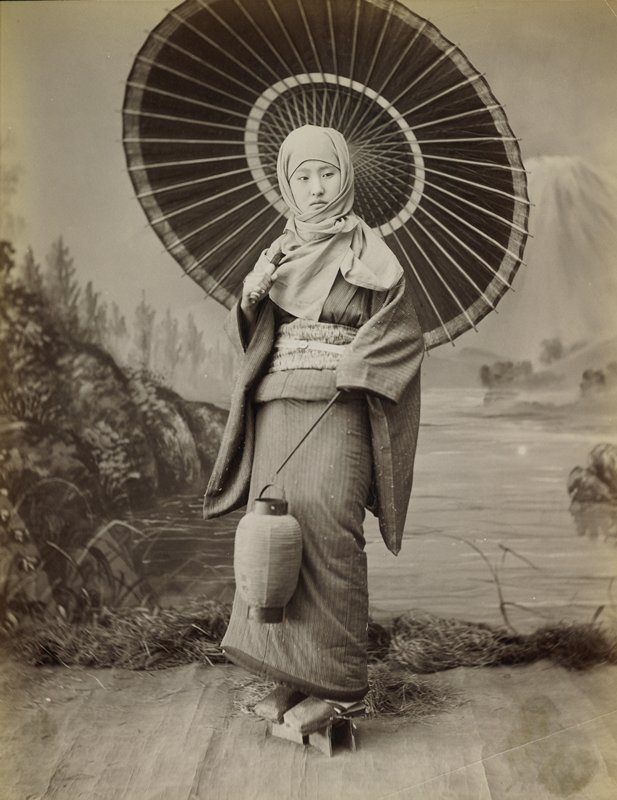 portrait of a standing woman wearing a striped kimono with a scarf wrapped around her head, carrying a parasol and a lantern on a stick