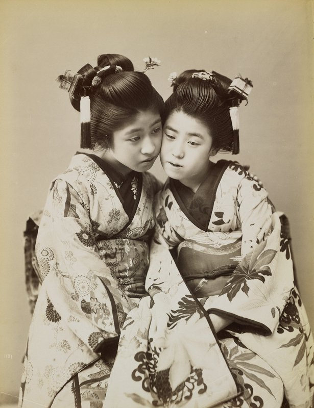 two girls wearing flowerd kimonos, seated snuggled next to each other, cheek to cheek