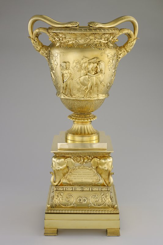 double-handled vase on fluted base; handles are each two snakes with heads resting on rim of vase; relief designs of grapevines, clusters of grapes and leaves; vignette of soldiers and native peoples on each side--soldiers and natives trading guns on one side, natives and soldiers with horses on opposite side; separate square stepped base with scroll and floral designs, coats of arms, tributary text cartouches and high relief elephant heads at each corner