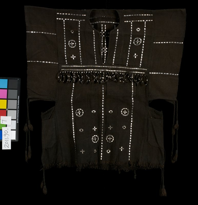 black eight paneled shirt with abstract design in metallic (aluminum) pieces; fringe with metallic trim in middle of chest; braided fringe 'net' with metallic pieces across bottom half of back; braided fringe with tassles at sleeve edges and at bottom side edges; side pockets below sleeve openings; vee neckline; short fringe at bottom edge; breast pocket on left side