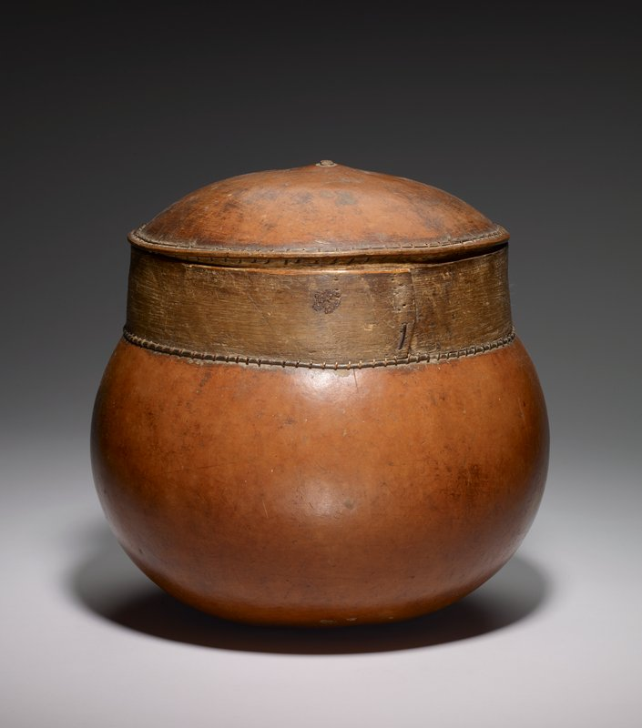 large rounded gourd container with straight vertical rim of wood, lashed onto top of gourd; slightly domed cover with similar vertical rim attached to cover in same fashion as body of vessel; golden brown patina
