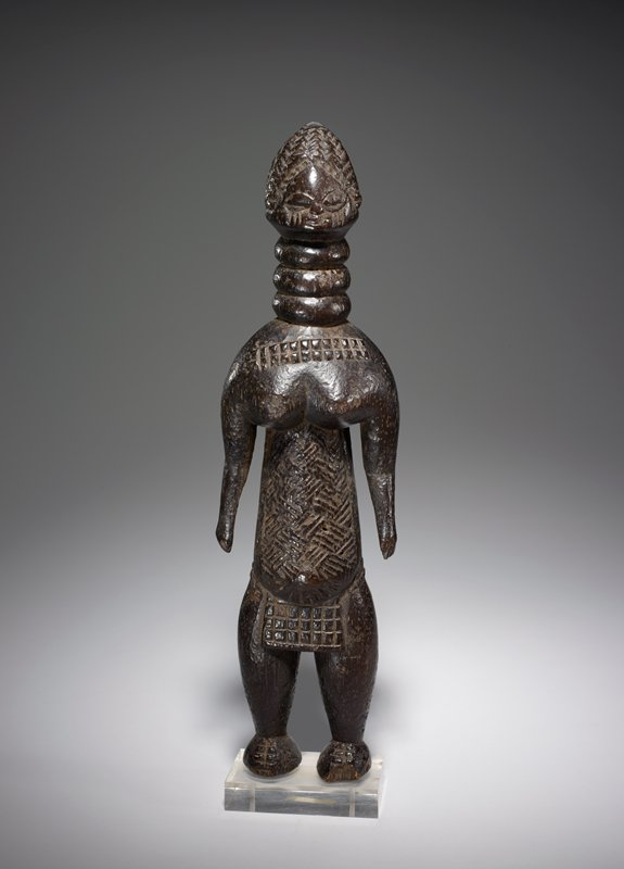 standing stylized female figure with small wedge-shaped head; three rings around elongated neck; large breasts; sloping shoulders; figure wears a small apron with a grid pattern; grid pattern on chest (scarification or necklace?); diagonal lines on abdomen and chest under breasts; stylized braided hairstyle; dark brown patina; attached to clear Plexi base