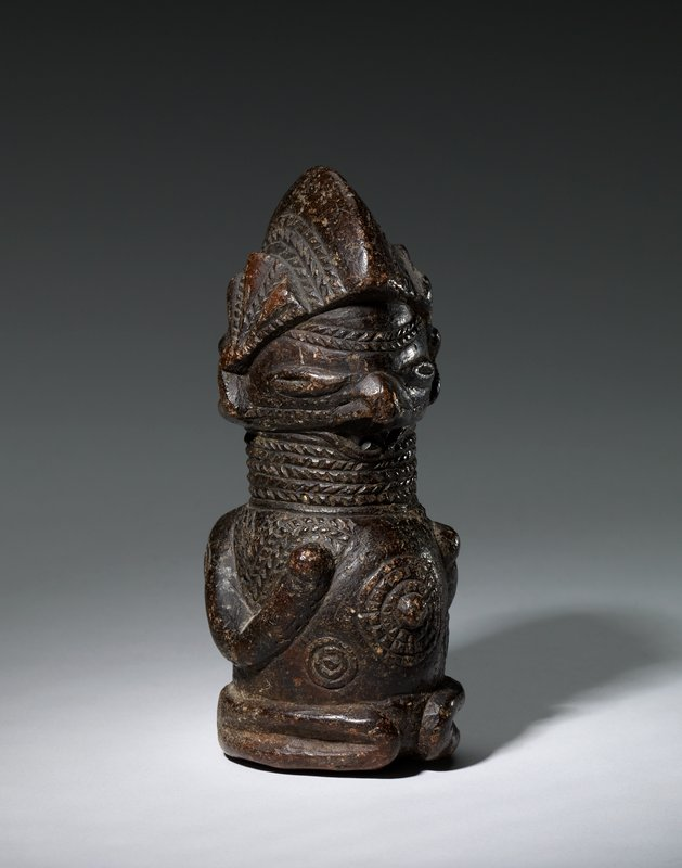 stylized figure with thin arms, hands held to chest; wearing helmet (or helmet-like hairstyle); cord-like bands around neck and similar patterning on forehead; narrow eyes; radiating, protruding belly button; radiating circles on arms and abdomen; dark brown stone