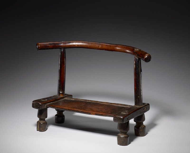 low stool with short spool legs; back of seat decorated with carved repeated diamond band; low curved horizontal backrest; medium brown patina