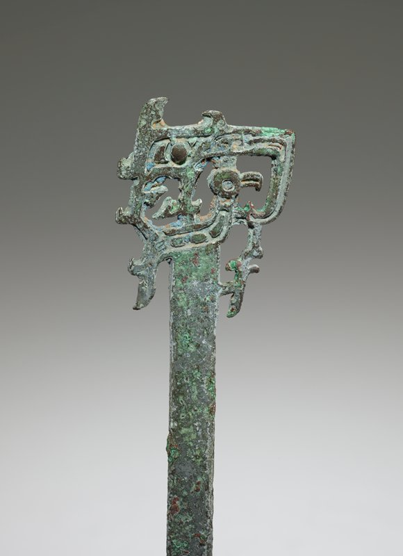 The purpose served by this implement is unknown, but it is possible that it was used for stirring wine. A highly complicated combination of animal motifs occurs in openwork on the handle. This handle, in its entirety, forms a beaked head with the rod serving as the body. As it approaches the handle, the rod displays a leg with a tuft and claw which rises to touch the beak of the bird. The handle itself divides into one bird whose crest supports the belly of a dragon. The dragon turns its head to the left, showing the teeth in its open mouth. For clarification of this involved composition, see Katrlgren Number 76, figures 70,71, 72. This composition occurs frequently in dagger axes, e.g., Karlgren plate 99 (50.46.15 and 50.46.67). Patina green