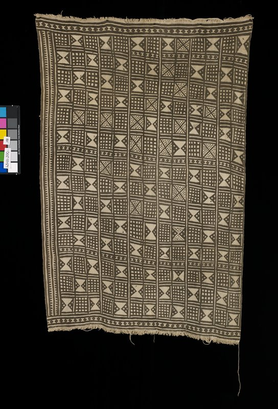 multi-paneled brown and cream skirt with abstract motifs of various sizes of triangles, squares, circles; fringe at either end