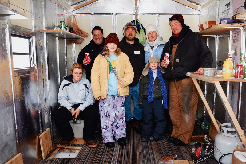 LON139188; caption: USA. Minnesota. Minneapolis. Winter Games. Ice Fishing. L to R, Tabby Allers, Neil Frandsen, Sammy Diemert, Dan Diemert, Casi Diemert, Gabrielle Diemert and Joe Johnson. 2012.; color image of seven people wearing winter clothing posing for photograph inside ice fishing house; woman at L holds fishing rod towards small hole in floor and ice; heating lamp, propane tank and various food/drink items at R
