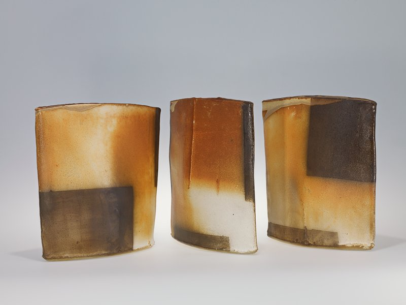three separate ceramic pieces, each with a football-shaped concave base and two sides, slightly flaring outward to point with a vertical seam from point to base (#1 and #3), or upward to rim (#2); very narrow top openings; each piece has motifs of brown rectangular and square forms with mottled orange and cream ground