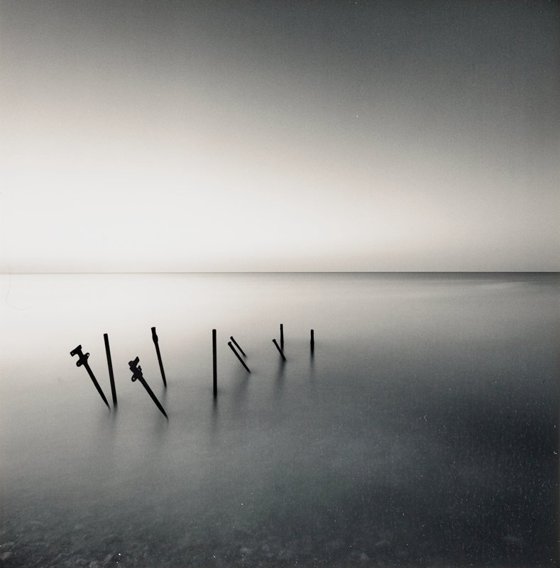 leaning black pole silhouettes in misty water