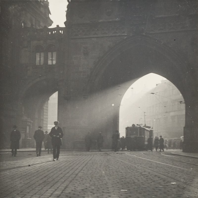 streetcar beneath a pointed arch at right in middle ground; pedestrians on street in middle ground; cobblestones; sun shining through archways