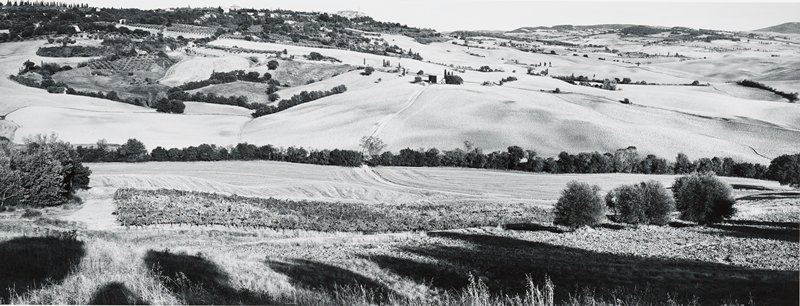 rolling farmland with fields; village at top left of center on high horizon line