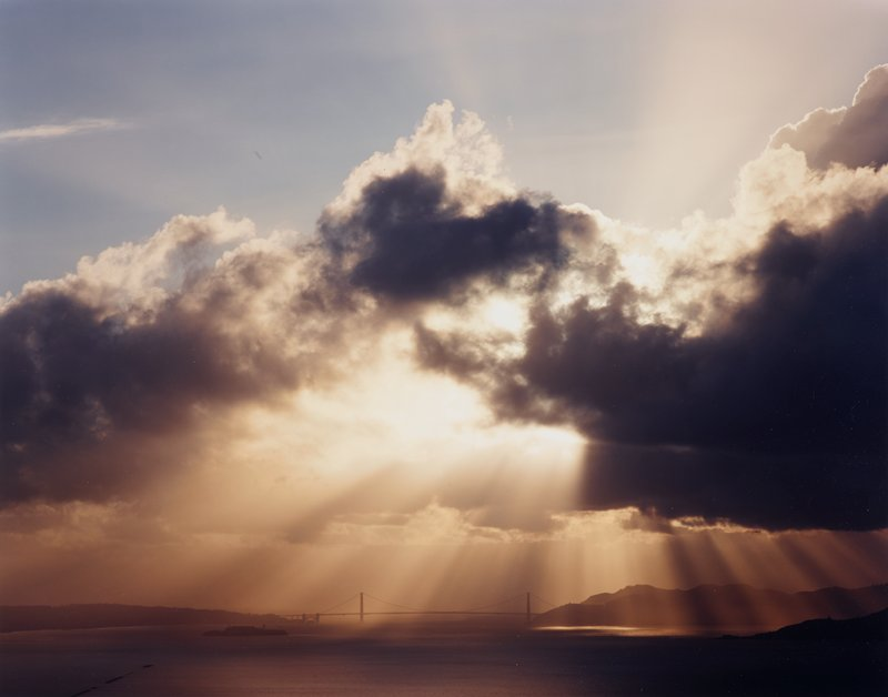 view of suspension bridge (Golden Gate?) across water; island at left; low horizon line; sunbeams through clouds at center, with blue sky above clouds at top