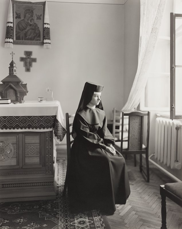 young nun seated on a side chair at center, looking out an open window at right