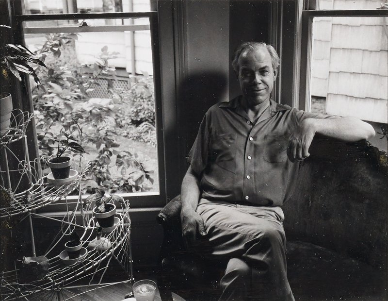 portrait of Minor White seated on a sofa in a corner in front of two windows; white wire plant stand at left; taped with masking tape on left and right edges to back of shiny paper mat