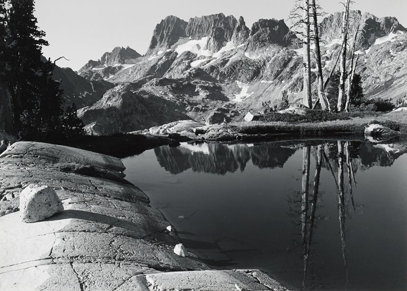 rocky, snow-covered mountain peaks in background; water in LRQ; rocks on short in LLQ, with long cracks; cluster of dead trees, URQ; pine trees, ULQ