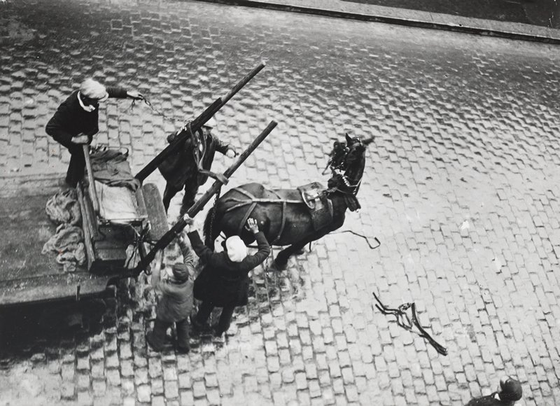 view from above of four figures unhitching horse from a cart, on a brick street; one figure standing on cart