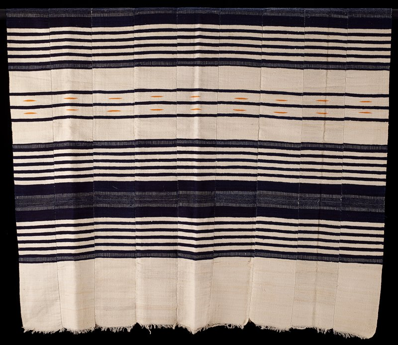 nine strips sewn together; cream with blue stripes of various sizes; four stripes have golden yellow elongated football shapes (spindles)