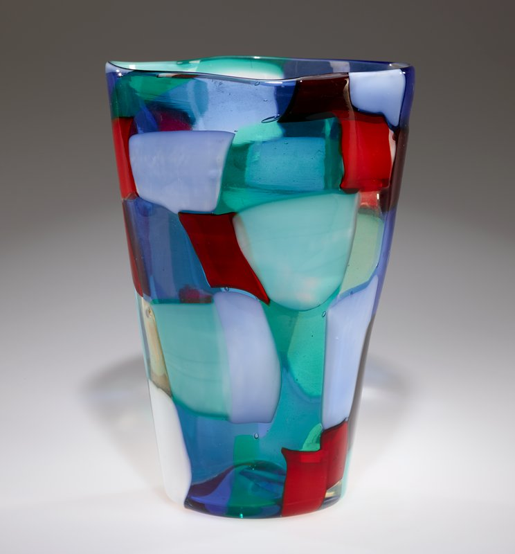 concave bottom; outward-flaring, irregular cylindrical shape; predominately roughly rectangular patchwork of colored glass--red, greens, blues, white, black and clear