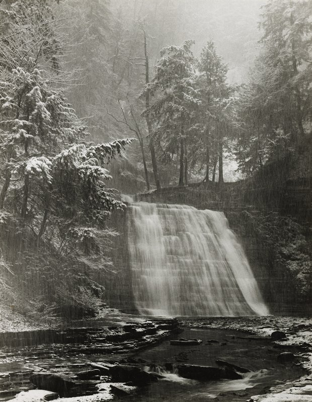 waterfall at center; rocky stream in foreground; snow-covered pine trees