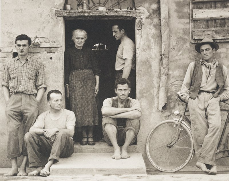 five men, one woman, standing in doorway, leaning on walls, seated of doorstep; man at right leans on bicycle