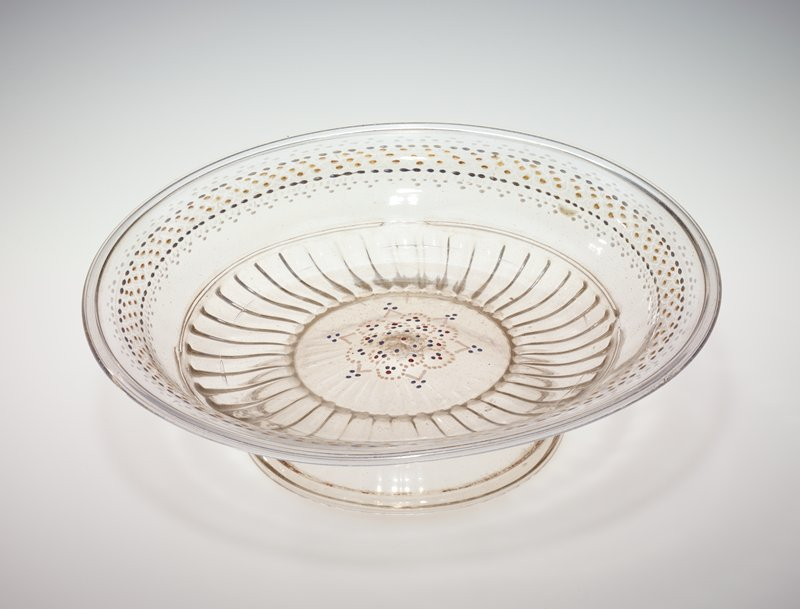 clear glass; shallow bowl on a wide, short foot; fluted band on underside of bowl around foot; tiny lozenge-shaped spots of silver, gold and white (red, blue and white on back) enamel around underside of rim; blue, red and cream (gold, cream and blue on underside) floral medallion in enamel spots and lines at center bottom