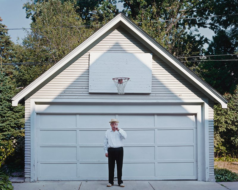 photograph of a man in a hat smoking a cigar in front of a white garage with a basketball hoop