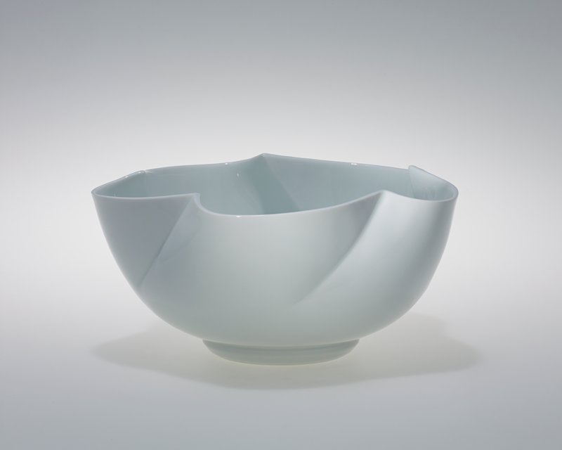 white; medium-sized bowl with five curving scallops, leaning diagonally at rim; wide ring foot