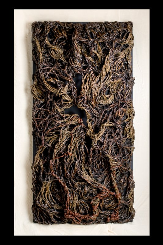 large rectangular form made of woven, braided, overlapping masses of bamboo rope; mounted to black board