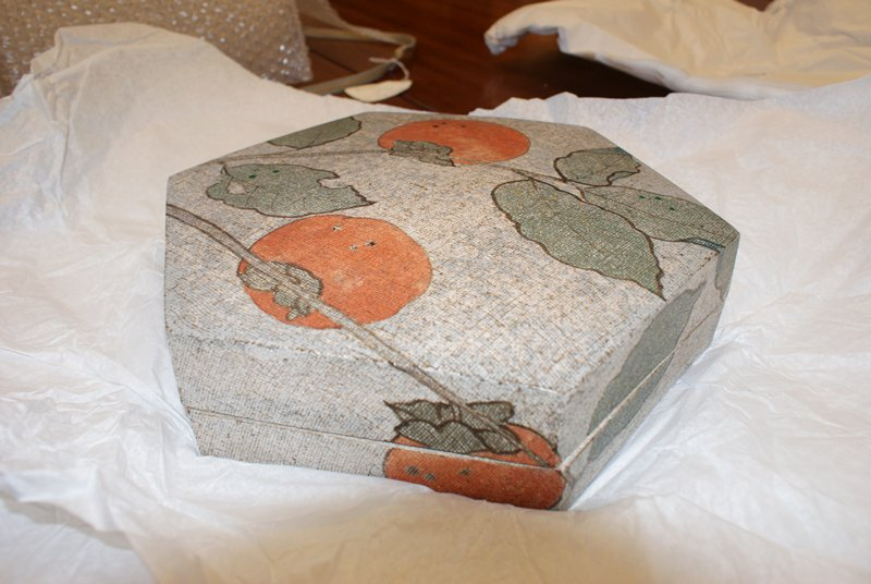 hexagonal stoneware box; grey background, painted with persimmon decoration; three acorns painted inside bottom; cloth imprinted texture