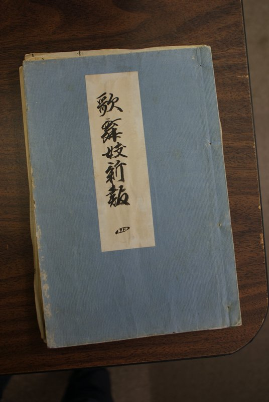 blue covered book; kabuki scenes and text inside; brightly colored images