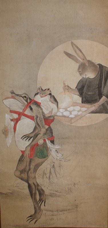 frog at LL strutting on two long legs, holding open fan in PR hand, balancing white mochi in mouth; young frog swaddled to back with red cords carrying bag of mochi balls; rabbit in black robes in round vignette at UR fanning tray of white mochi balls