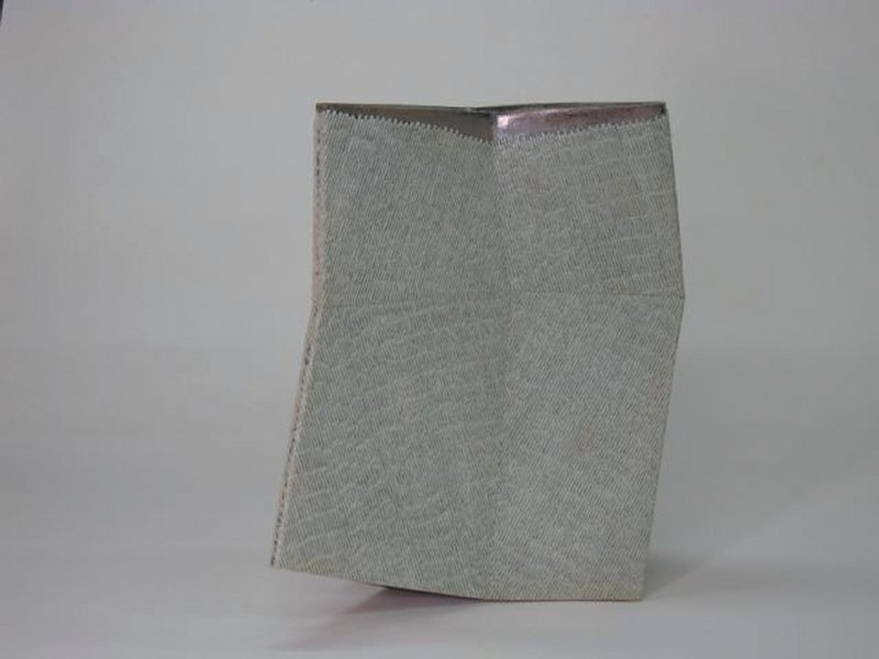 chevron-shaped ceramic vessel with irregular geometric walls; pattern of tiny, pale green bars