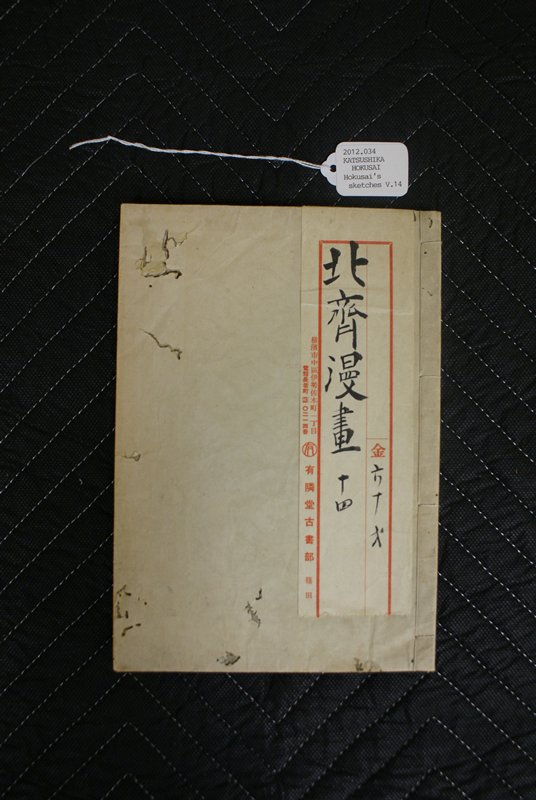 white cover with white pattern and Japanese label at R; variety of partially colored images inside including landscapes, people, and animals including dogs, cats, mice, and a camel