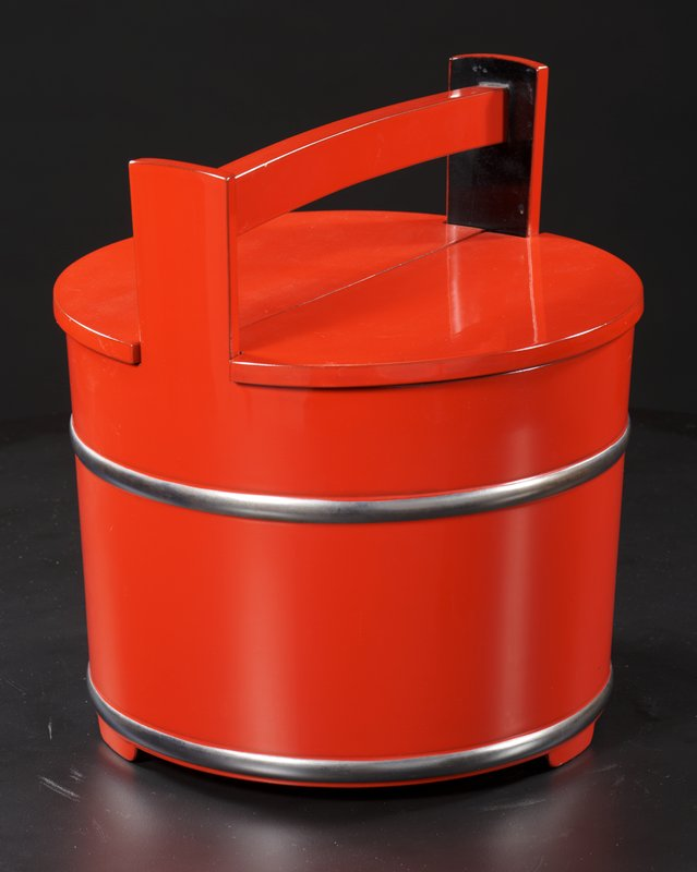 red lacquered bucket with three short feet; two raised, silver tinted bands around bucket, one at bottom and one near top; squared handle; black interior; two-piece lid