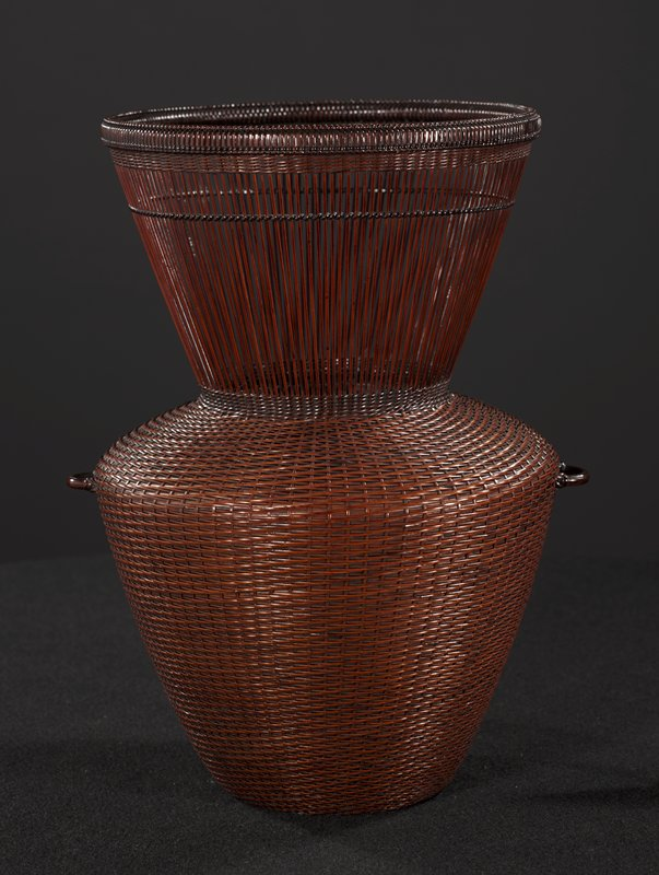 flower basket with very wide mouth; dramatically tapering, vertical open woven neck; closed weave body widens below neck, tapering again at base; bamboo cylinder with copper lining