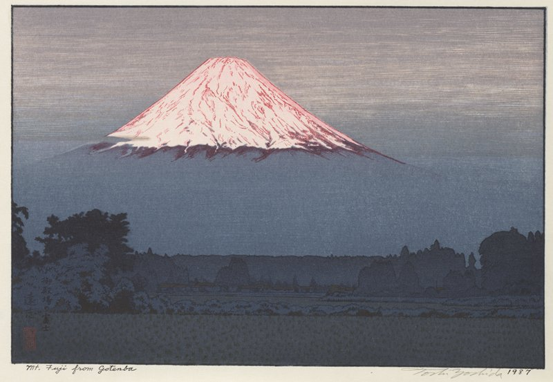 peak of Mt. Fuji glowing pink; grey sky and blue-grey landscape with silhouetted trees