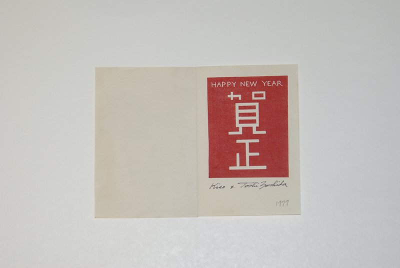 front: two zebras standing side by side at L, each looking in opposite direction; orange background with orange and gray tree in ULQ; inside: red block with New Year's greeting in English and Japanese; separate yellow sheet with printed New Year's greeting and signature