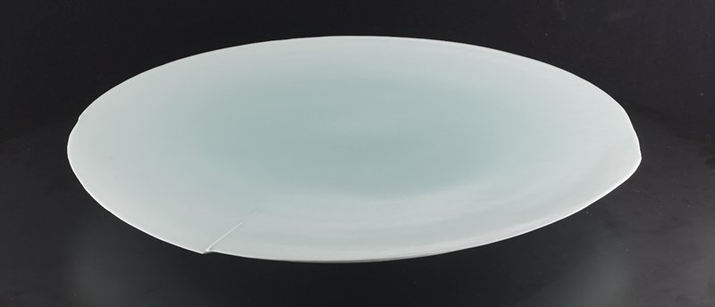 "large, round, flat plate with light blue-green glaze; glaze is darker at center; broken, linear, raised ""ripple"" near edge; slightly conical form"