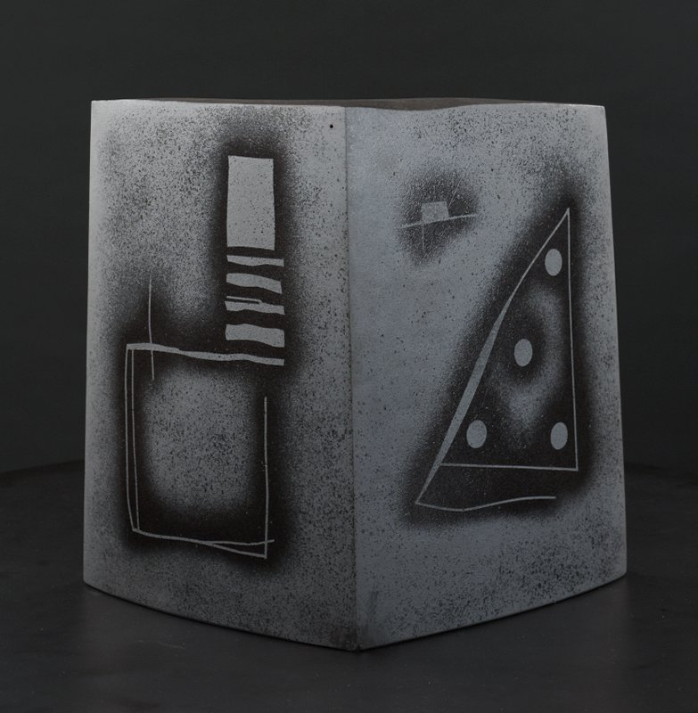 triangular black form with triangular shadow-like extension on bottom; white outline across front top of form with vertical outline extending down from top center, and another extending inward from bottom point; black geometric forms and patterns in glaze